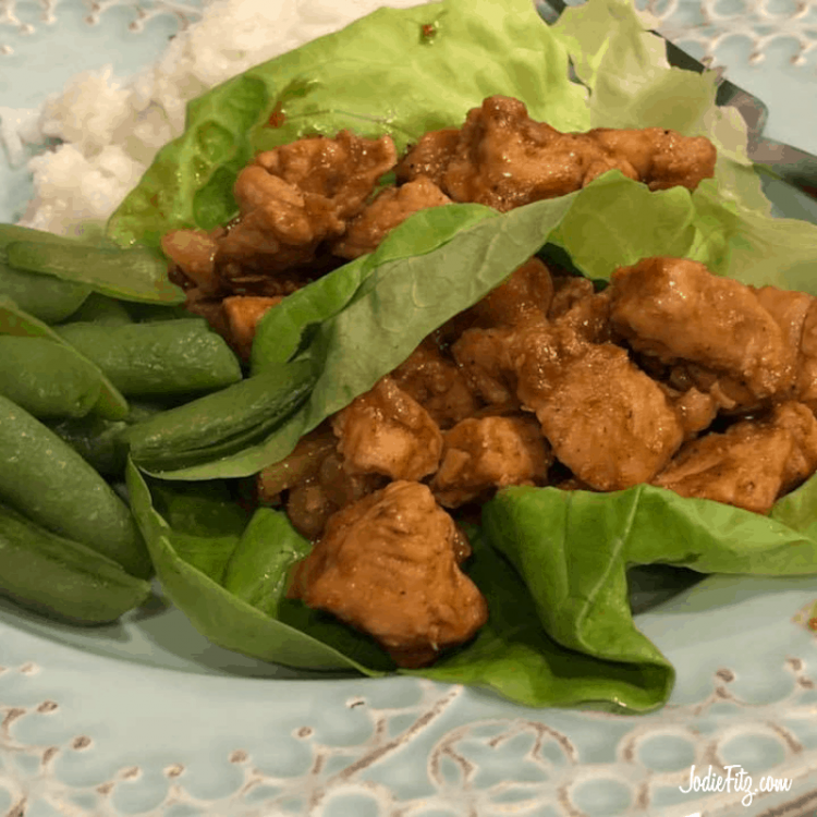 An Asian inspired seasoned chicken in a lettuce wrap with sugar snap peas and rice on the side