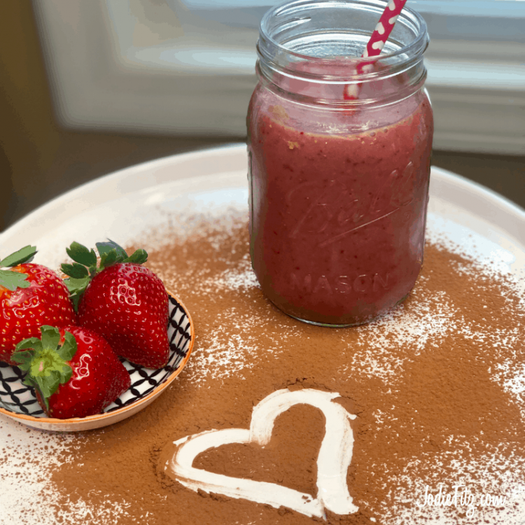 A chocolate strawberry smoothie in a bell jar with a red paper straw with white hearts, a dish of fresh strawberries on a white plate dusted with cocoa powder and a heart drawn in it