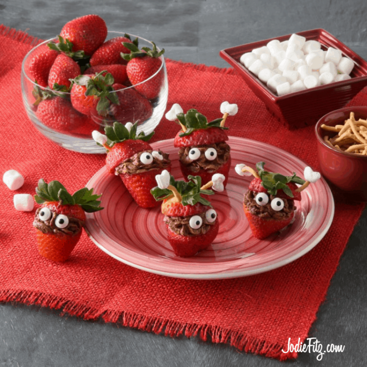 Strawberries stuffed with a chocolate whipped mousse with candy eyes on the mousse and the top of the strawberry with greens used as a hat and little antennas made of Chinese noodles and mini marshmallows