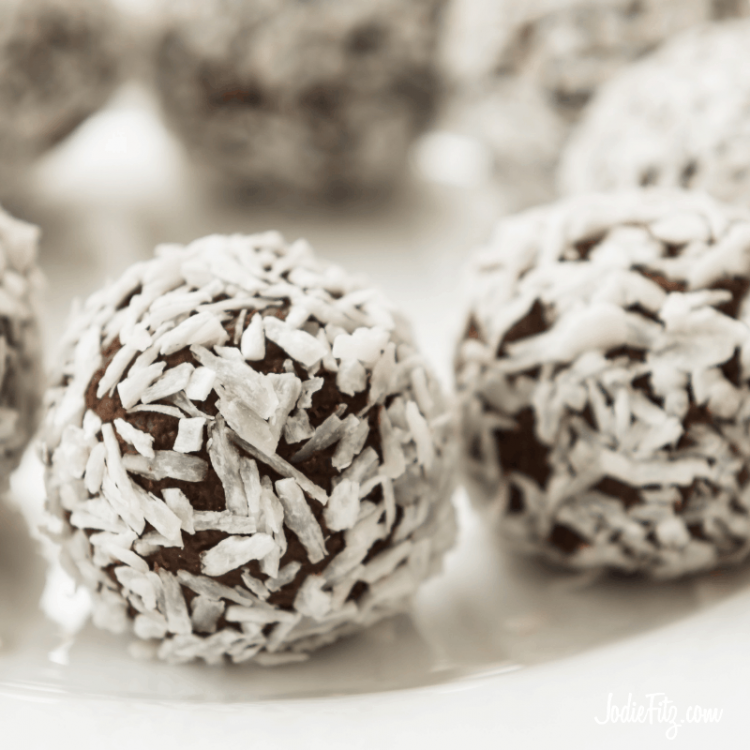 Coconut energy bites made with dates and unsweetened cereal rolled in coconut flakes on a dish ready to be served