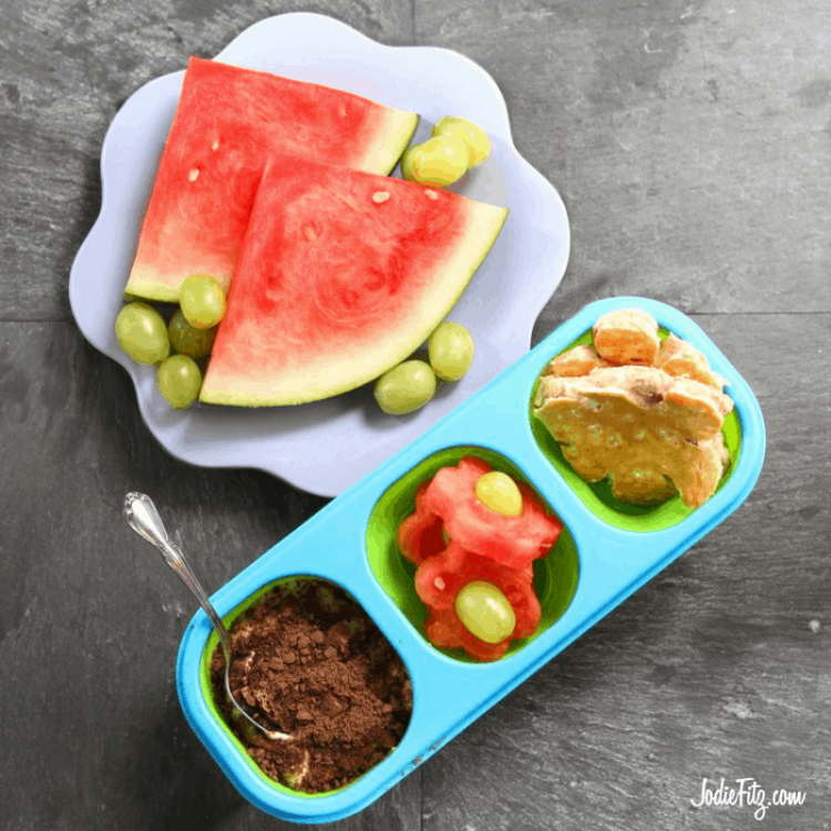 A lunchbox packed with a healthy version of dirt dessert, watermelon cut in the shape of flowers with green grapes in the center with sandwiches cut in the shape of flowers