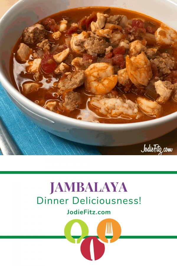 A white bowl of colorful jambalaya made with turkey sausage, chicken, shrimp, tomatoes and green bell peppers served on rice