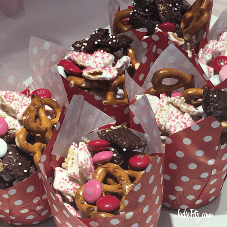 Valentine snack mix made with white chocolate and dark chocolate covered check cereal, pretzels and red, pink and white M & M candies served in cupcake liners