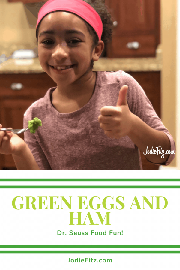 A young girl with a smile holding a fork full of green eggs and ham in one hand and her thumb up on the other hand.