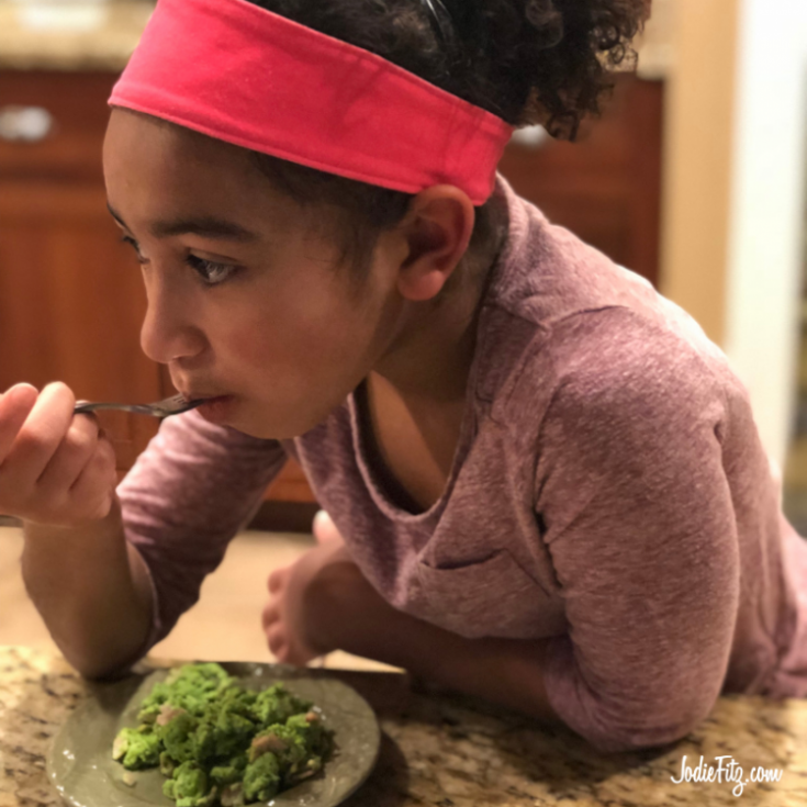 A young girl taking a bite of green eggs and ham. The eggs are colored naturally with spinach.