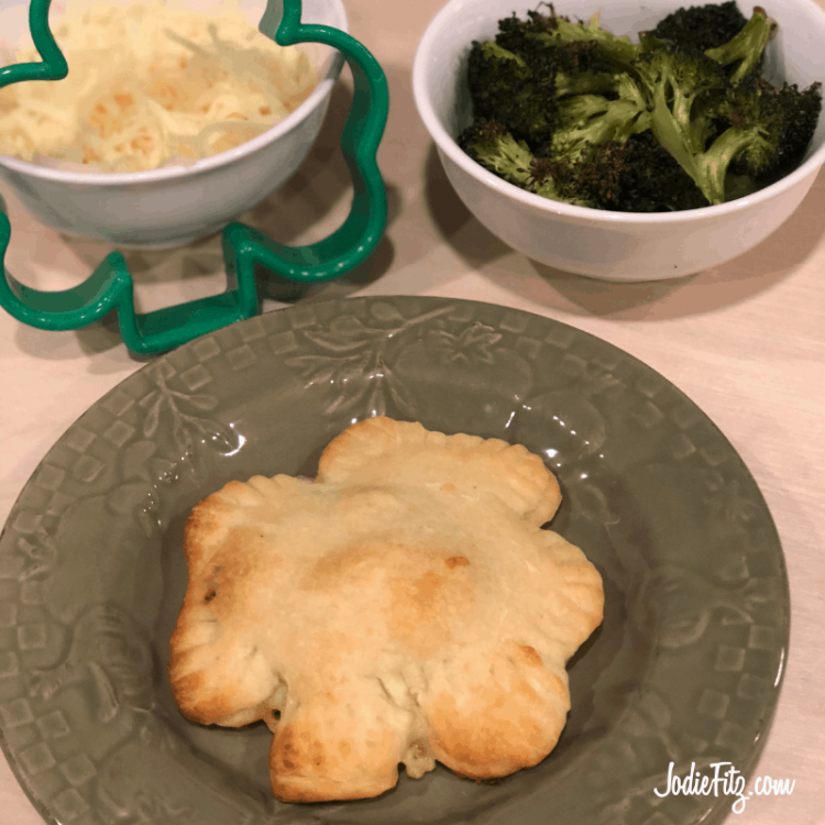 Shamrock shaped pizza pocket on a green plate surrounded by a shamrock cookie cutter, a bowl of cheese and a bowl of roasted broccoli