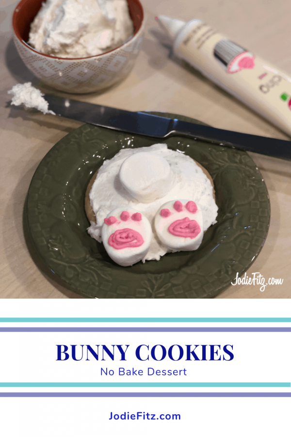 Cookie on a plate decorated to look like a bunny butt with a bowl of frosting in the background