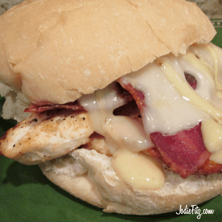 Chicken sandwich topped with melted Swiss cheese, cooked bacon and honey mustard sauce served on a hard roll