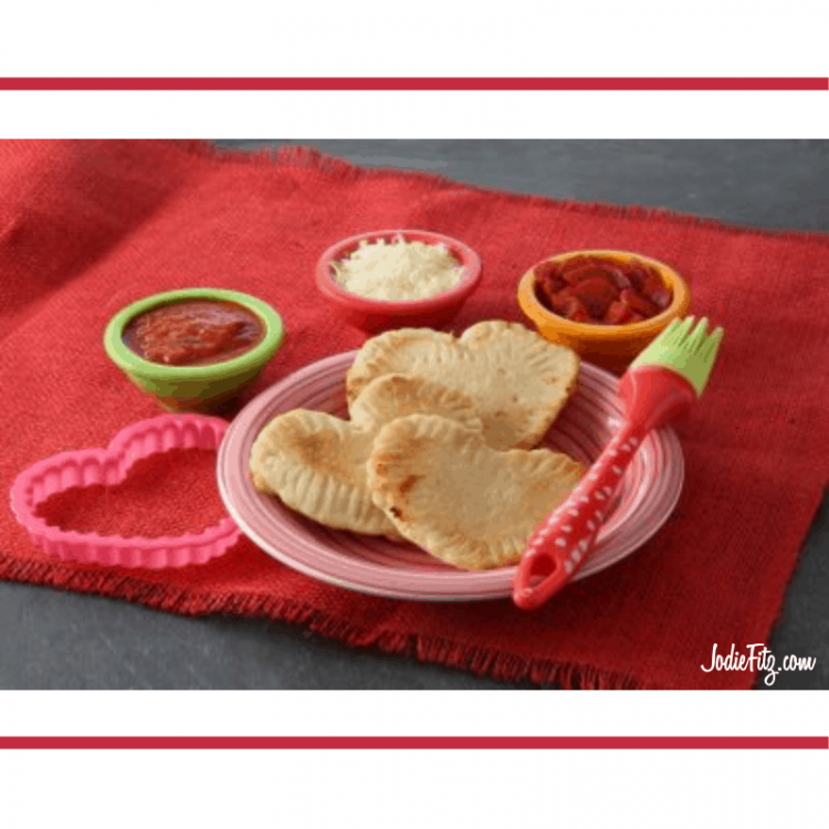 Three heart shaped pizza pockets on a pink plate surrounded by a pink cookie cutter, a bowl of sauce, a bowl of shredded mozzarella cheese and a bowl of mini turkey pepperoni's