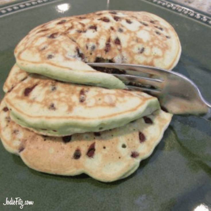 Stack of three mint chocolate chip pancakes on a plate with a fork
