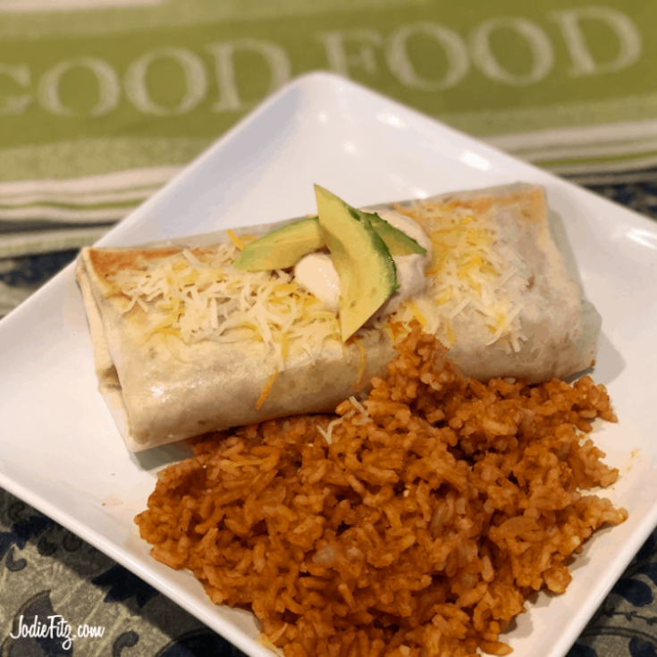 A burrito topped with cheese, sauce and fresh avocado slices on a plate served with Spanish rice