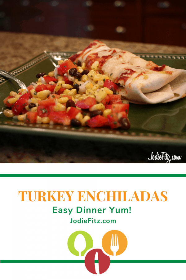 A turkey enchilada topped with enchilada sauce and melted cheese served with a mix of corn, red bell pepper, black bean and spices