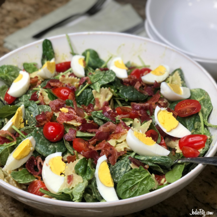 A large bowl of pasta, fresh spinach, grape tomatoes, bacon, hard boiled eggs and avocado sauce