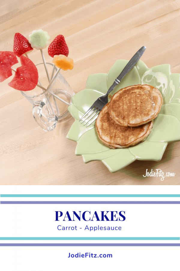 Pancakes topped with syrup on a lime green plate with fruit cut in the shape of flowers