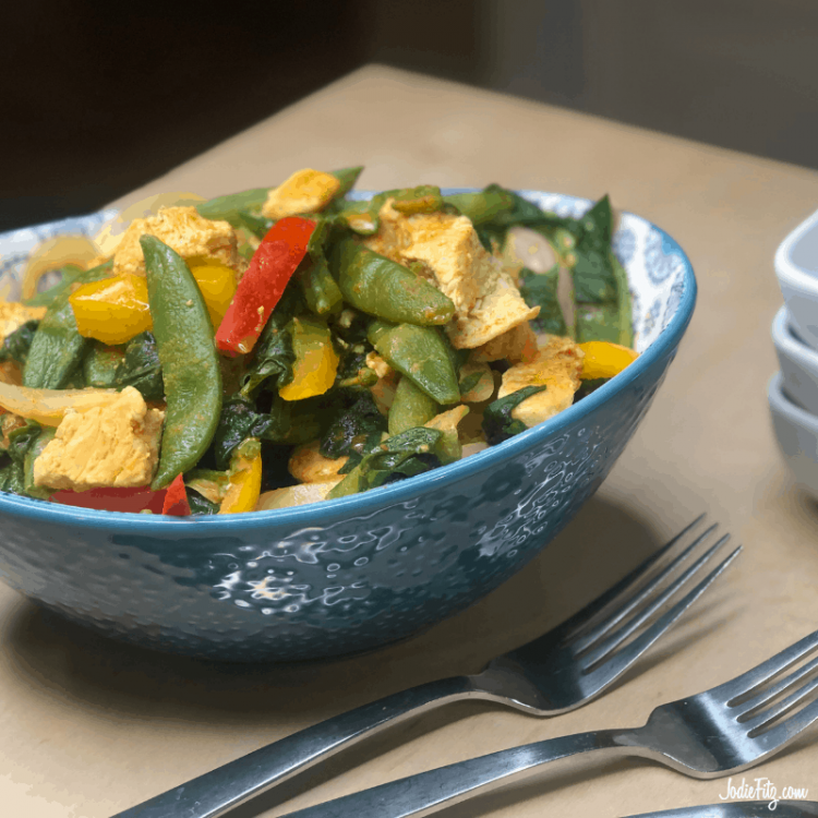 Bowl of chicken curry made with red peppers, yellow peppers, spinach, chicken and sugar snap peas served on rice