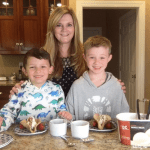 A mom with two boys making dessert tacos