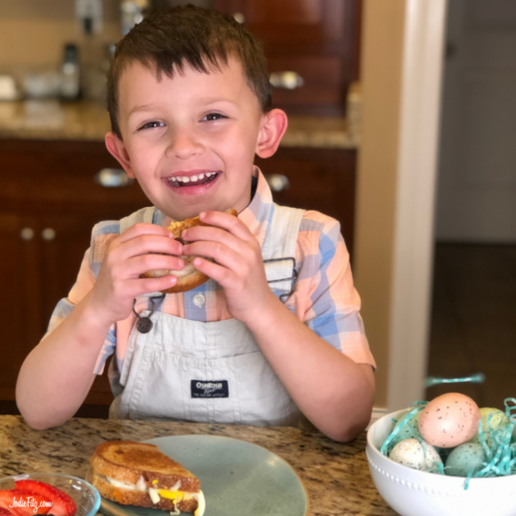 A young boy about to bite into a grilled egg and cheese sandwich
