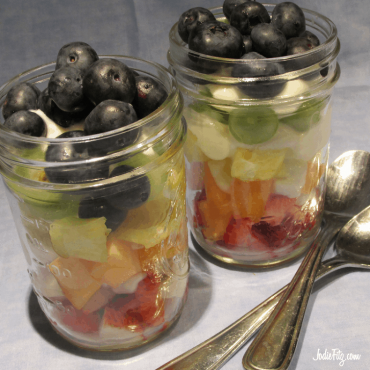 A mason jar with layers of colorful fruit and yogurts including strawberries, oranges, cantaloupe, pineapple, honey dew melon and blueberries