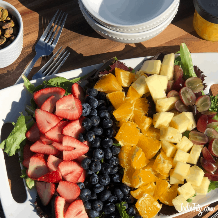 Tray of salad with with spring mix lined with fresh cut strawberries, blueberries, oranges, pineapple, grapes and beets