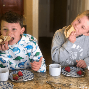 Two young boys eating dessert tacos filled with ice cream