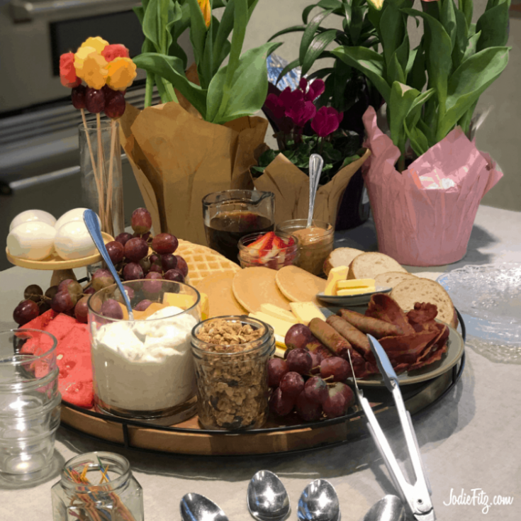 A large tray filled with breakfast items served for a breakfast buffet including assorted fruits, supplies for yogurt parfaits, pancakes, waffles, toppings, breakfast meat assortment and hard boiled eggs