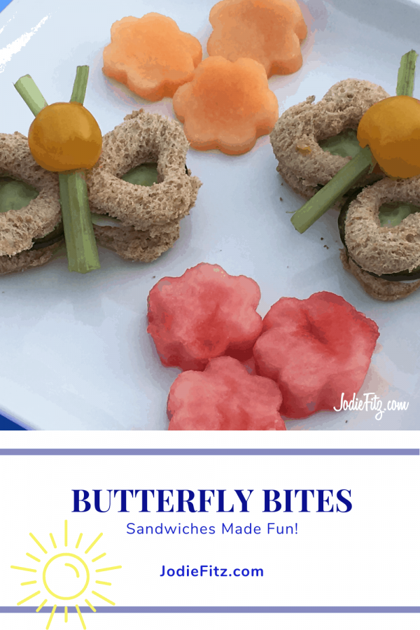 A plate with two veggie filled mini sandwiches in the shape of a butter fly with flower shaped cut watermelon and cantaloupe fruit pieces
