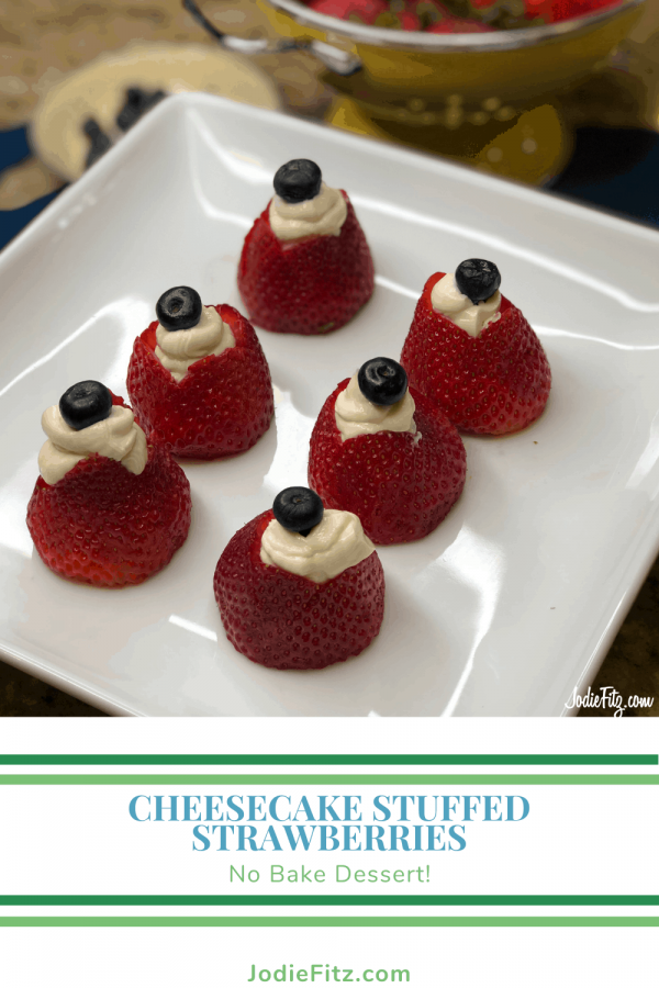 A plate with strawberries that have been hollowed and filled with a cheesecake flavored filling and topped with a fresh blueberry