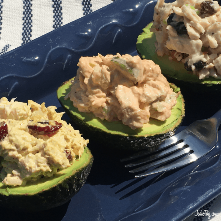 Three avocado halves filled with different chicken salads on a platter