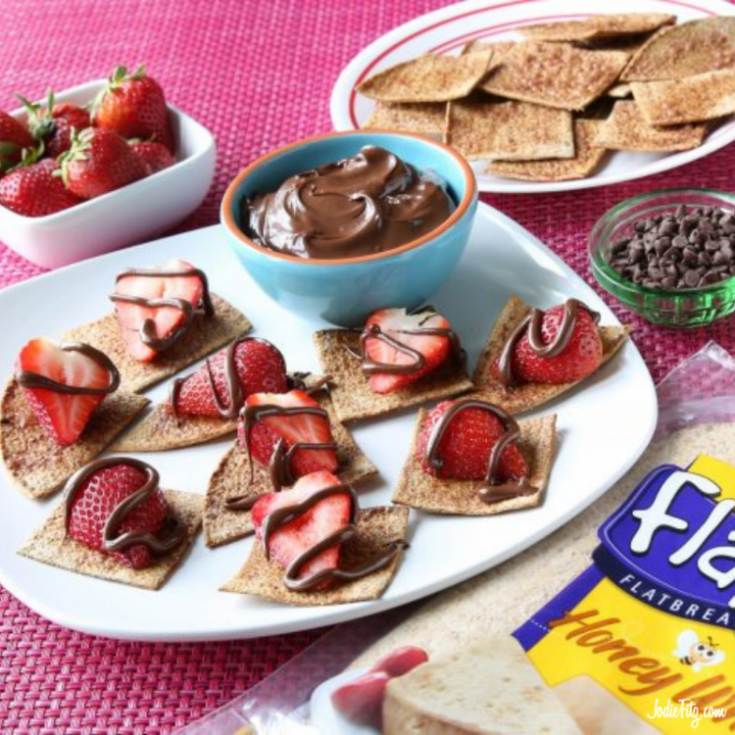 Homemade cinnamon flatbread chips topped with fresh strawberries and a drizzle of chocolate on a tray ready to be served