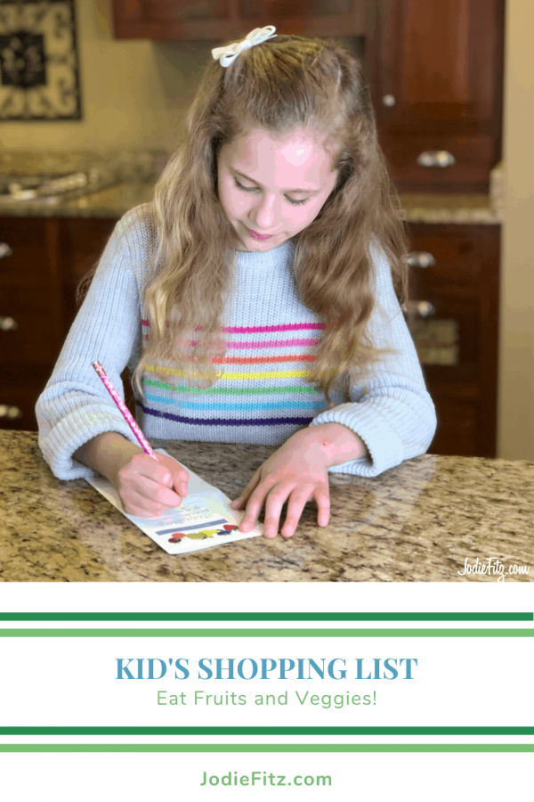 A young girl writing out a shopping list of food items