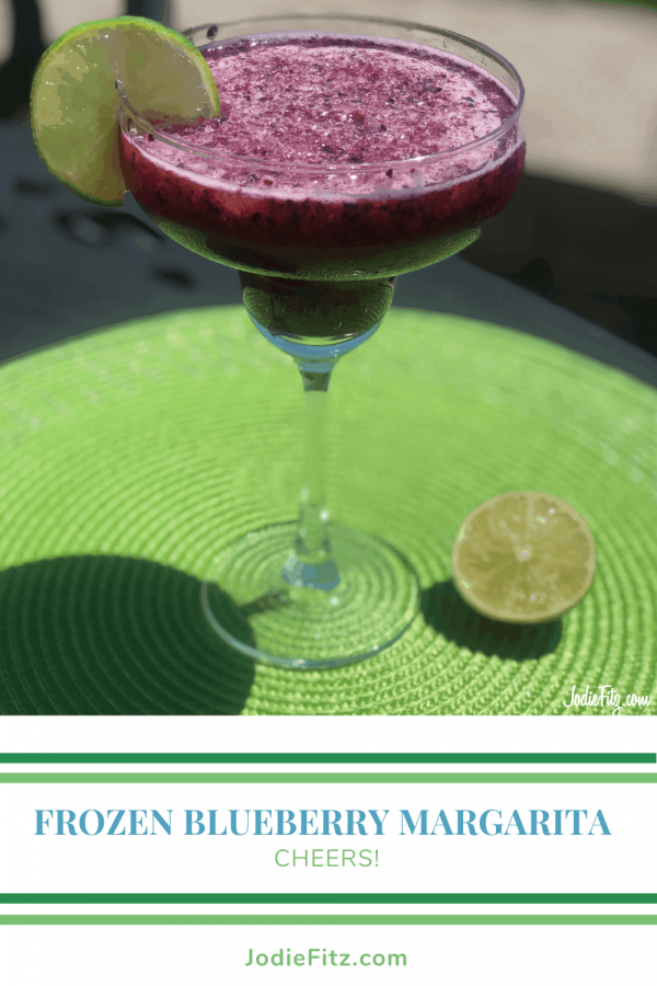 A margarita glass filled with a frozen blueberry margarita with a wedge of lime on the rim of the glass
