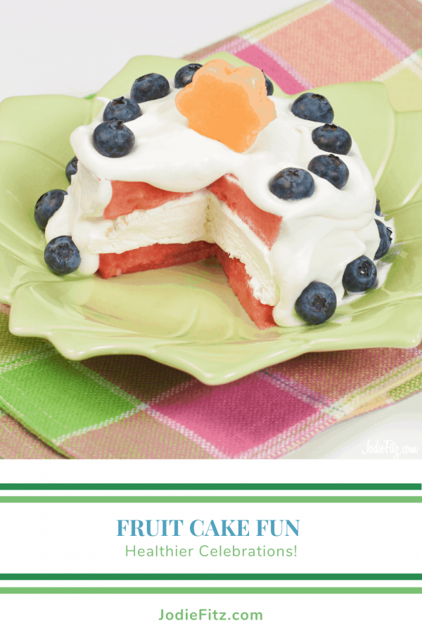 A cake made of Layers of watermelon with a whipped topping frosting and decorated with fresh blueberries and a piece of melon cut into a flower