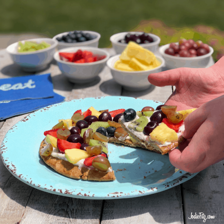 A plate with a fruit pizza topped with pineapple, grapes, strawberries, kiwi, blueberries and cherries sliced and ready to serve