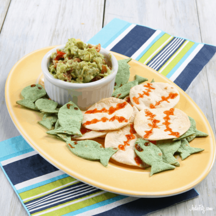Chips in the shapes of baseballs and fish with homemade Guac on a serving tray