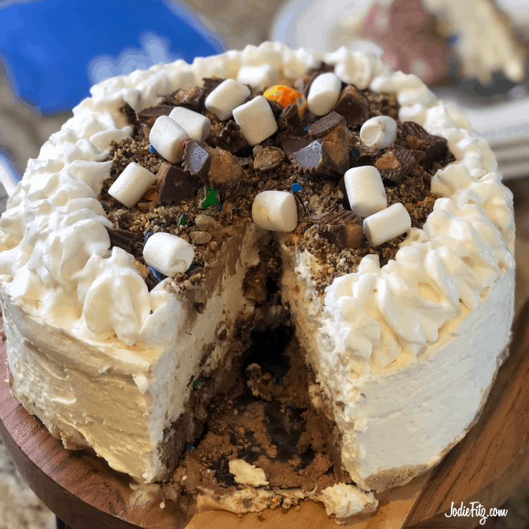 An ice cream cake topped with candies and mini marshmallows with a slice cut out of it