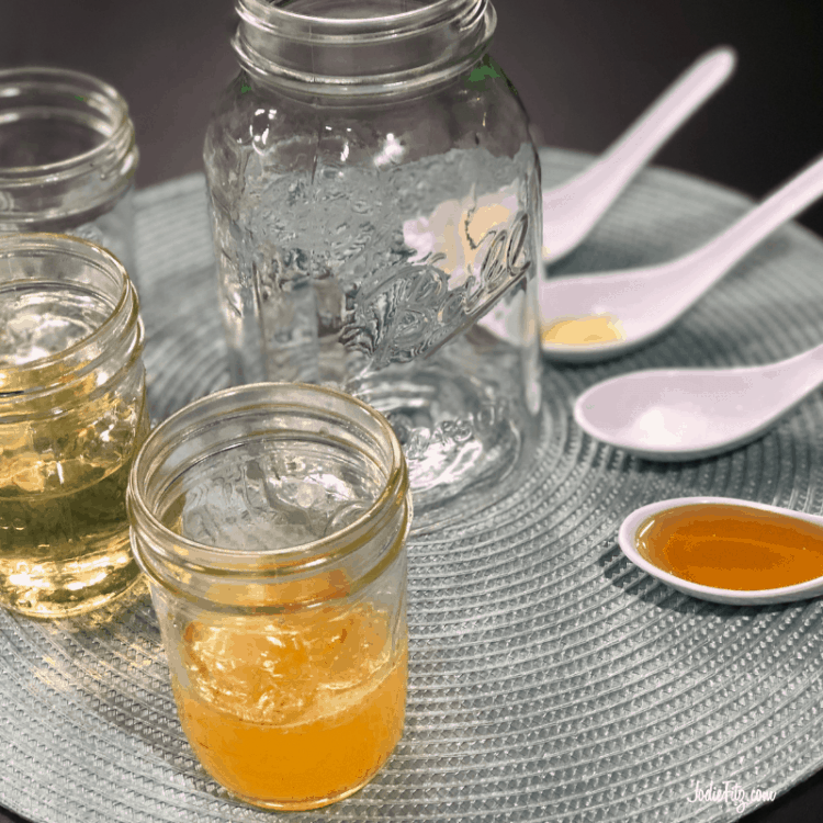 Ingredients and supplies set out on a table to make a homemade honey orange salad dressing