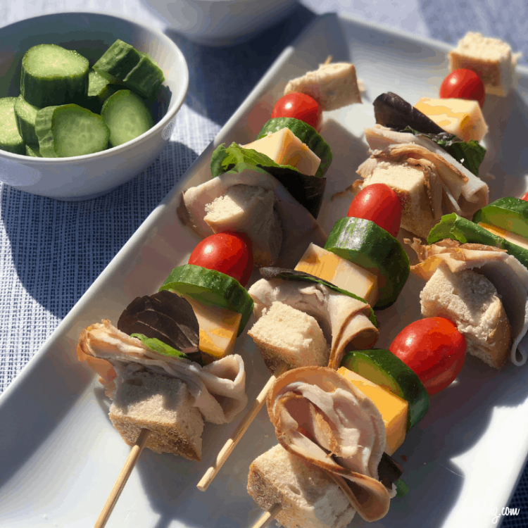 A plate with sandwich kabobs that included bagel pieces, meat, lettuce, cheese, cucumbers and tomatoes on skewers