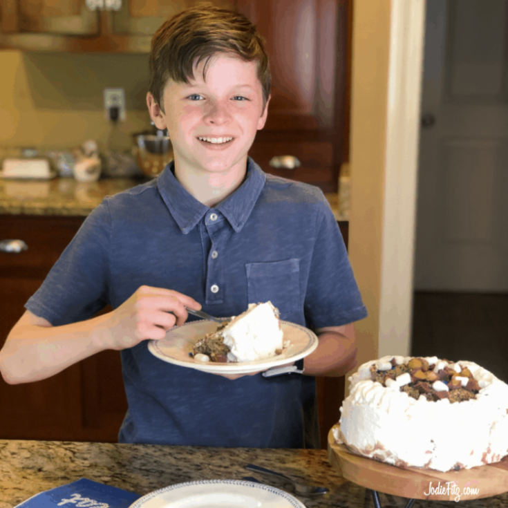 A young boy eating a piece of ice cream cake