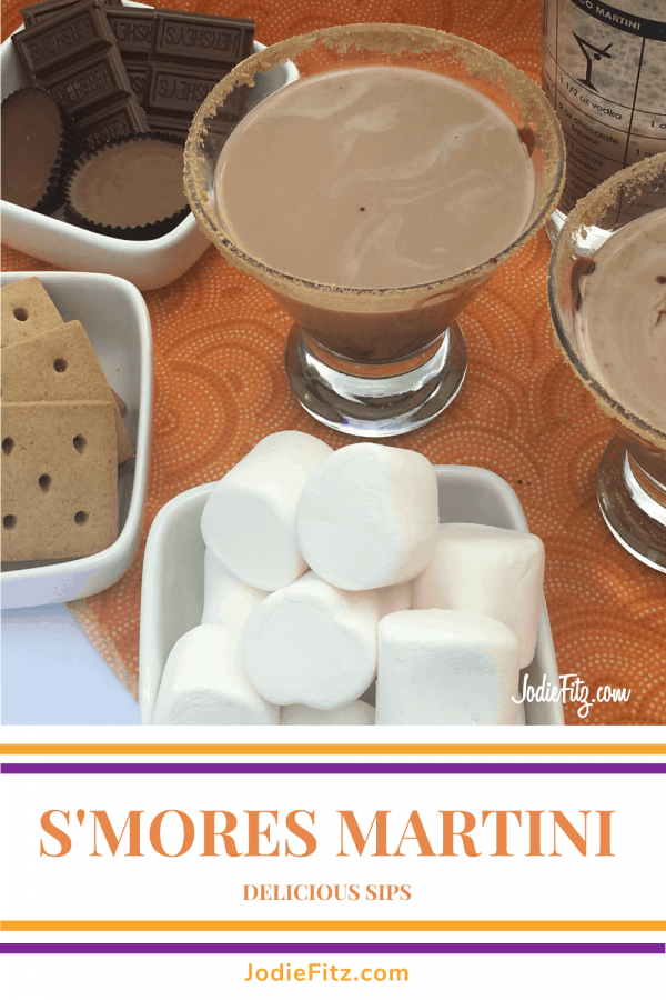 A s'mores martini in a martini glass with a graham cracker rim surrounded by a bowl of marshmallows, Reese's candies, graham crackers and a martini shaker