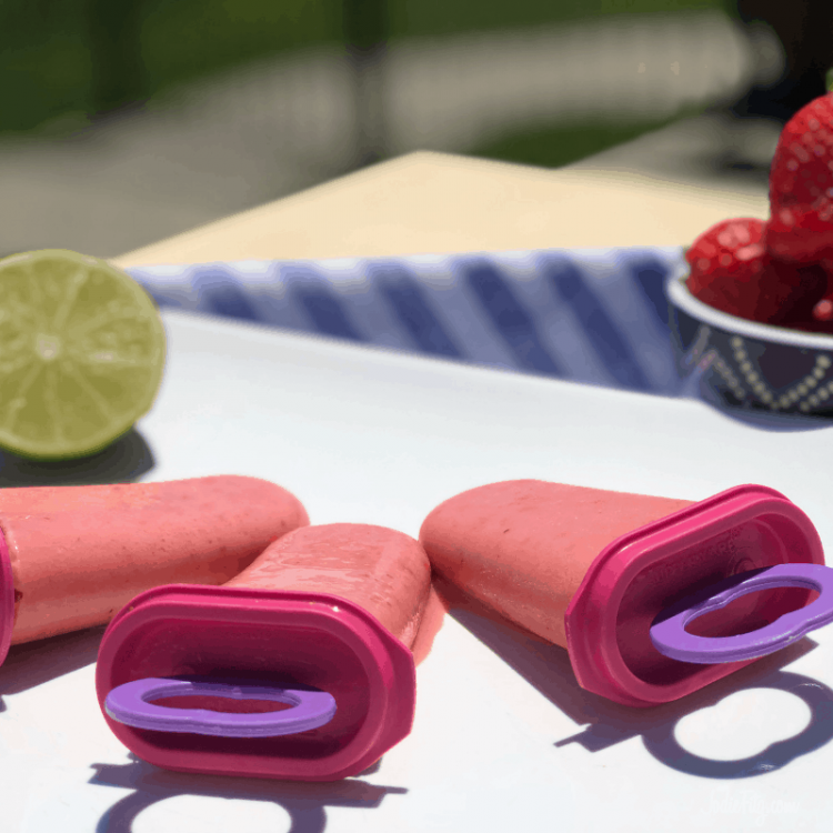 A white tray with three strawberry freeze pops ready to be served