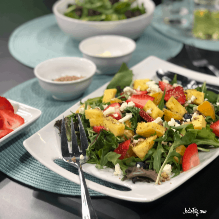 Arugula salad topped with fresh sliced strawberries, blueberries, fresh cut pineapple, orange slices, nuts and goat cheese