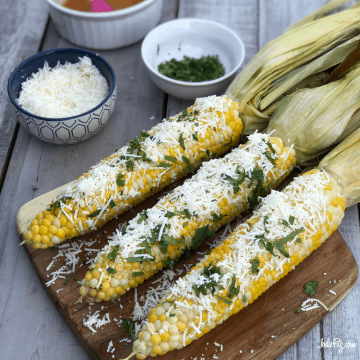 A wooden cutting board with three ears of corn topped with grated cheese and chopped cilantro