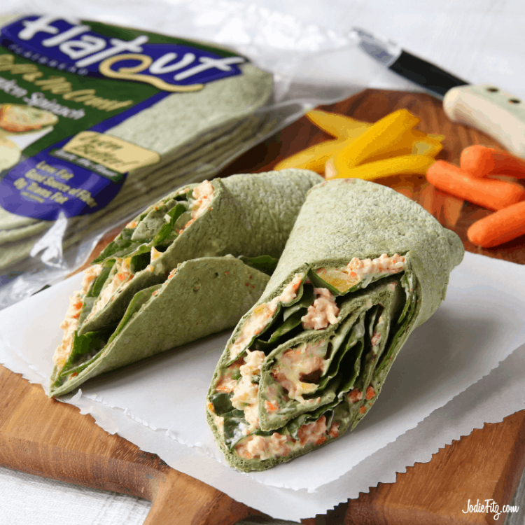 A spinach garden wrap filled with fresh vegetables and a veggie cream cheese spread cut and ready to be wrapped in parchment paper