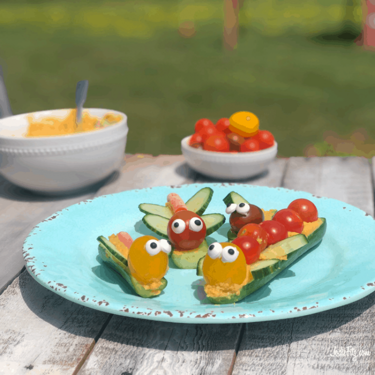 A plate with veggies bugs made out of mini cucumbers, carrot hummus, sliced cucumbers, colorful grape tomatoes, carrots and candy eyes