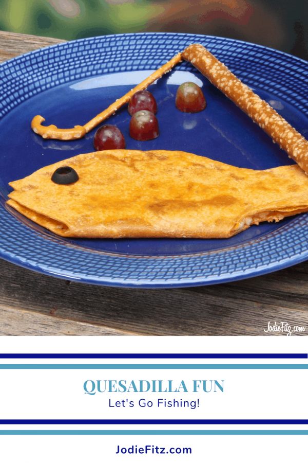 a tomato basil cheese quesadilla cut and shaped into a fish on a plate with grape bubbles and pretzels laid to create an edible fishing pole