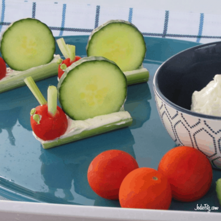 A snail shaped snack made out of celery filled with cream cheese, a slice of cucumber for the back, a grape tomato for the head & two tiny pieces of celery for antennae